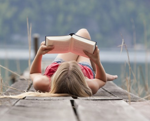 Austria, Teenage girl lying and reading book on jetty